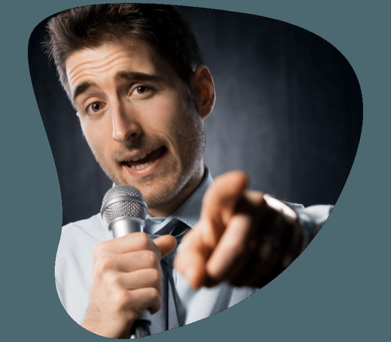 Magabiztos férfi mutat mikrofonnal a kezében
